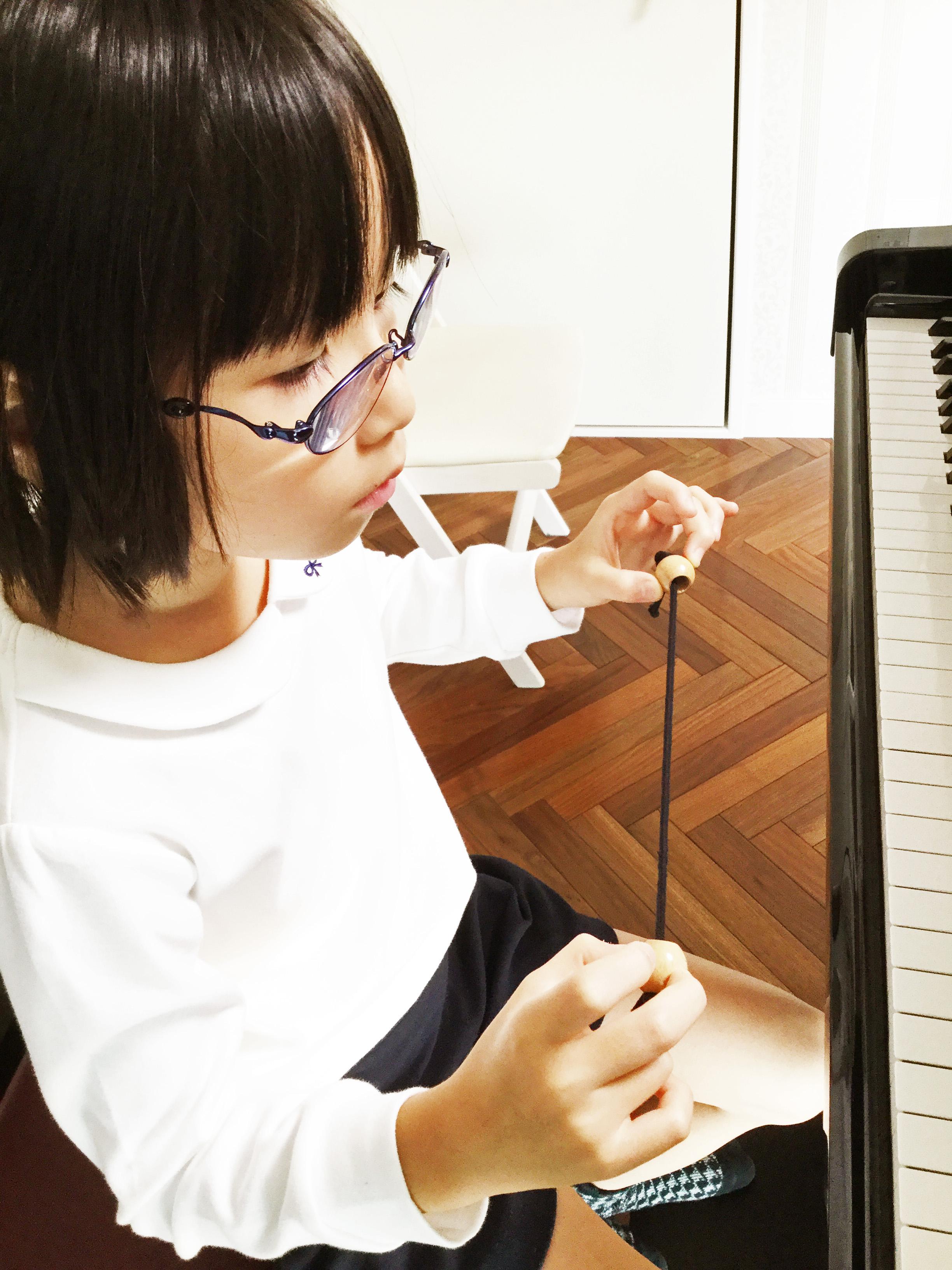玉つき紐を使って、演奏時の丸い指の形を習得